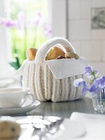 A white crocheted bread basket