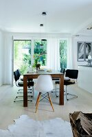 Solid wooden table and chairs in front of terrace doors in pale dining room