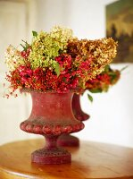 Bouquets of dried hydrangeas and spindles in stoneware vases