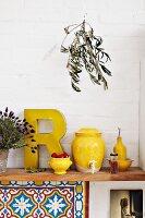 Yellow kitchen utensils such as vinegar pot and oil bottle on wooden shelf in Mediterranean kitchen