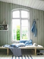 Maritime ambiance; lounger with beech frame and linen-covered mattress below window