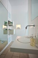 A modern, white bathroom with a wash basin, a wall mirror and drawers set into the wall