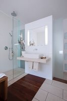 A modern bathroom in white with a basin, a glazed shower area and brown wooden inlays in the tiled floor