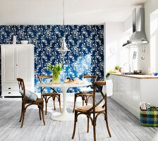 White, modern country house kitchen with blue and white wallpaper on one wall