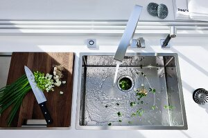 Chopped spring onions on a wooden chopping board next to a kitchen sink