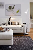 A living room decorated in light tones with a sofa, a floor lamp and pictures on the wall
