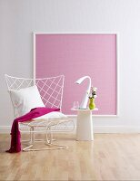 Wire chair and side table in front of pink wallpaper in picture frame