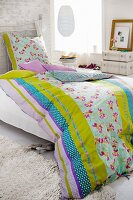 Bed with colourful, reversible bed linen