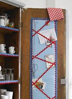 Hand-crafted, fabric note board with zigzag trim inside cupboard door