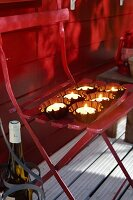 Lit tealights in small cake moulds on folding chair outside