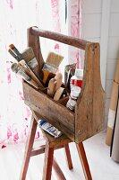 Various painting utensils in wooden toolbox