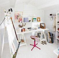 Desk and easel in artist's studio in Scandinavian summer house