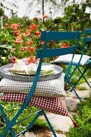 Cushions & tray on folding chair in summery garden