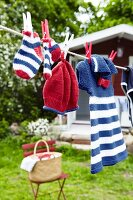 Knitted baby clothes hanging on a washing line in a garden