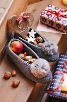 Felt slippers filled with nuts, apples and biscuits
