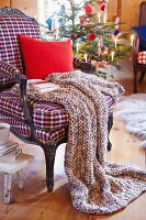 A knitted blanket, a cushion and a book on an armchair with a Christmas tree in the background