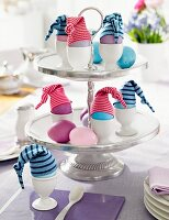 Easter eggs with little hats on a cake stand