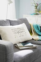 Cream scatter cushion embroidered with mother-of-pearl buttons on sofa
