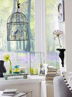 A bird cage, a wall console, a picture on the wall and various decorative objects on the window sill in the corner of the room