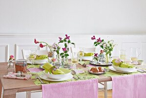A table set for spring with pink table runners, pastel-green place mats and napkins