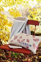Printed linen cushion on folding chair in autumnal garden