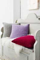 Knitted cushions with a braided pattern made of cashmere wool on a wooden bench