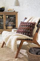 A blanket and a knitted Jacquard-style cushion on a chair