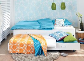 Bedclothes in a colourful pattern mixture on a pulled-out guest bed with a delicate floral-patterned wall design in the background