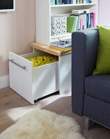 A bookshelf in a living room with a drawer on the side for extra storage