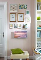 A small picture gallery of drawings with a television on the wall next to a bookshelf