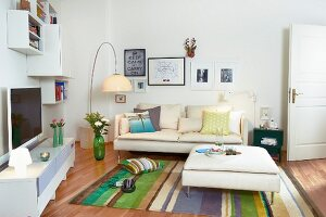 White media cabinet, wall-mounted shelves, cream sofa, ottoman and striped rug