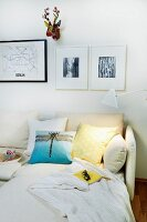 Photos and colourful, stylised hunting trophy in corner above comfortable sofa