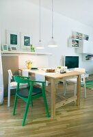 A dining area in an open plan living room, a simple solid wood table with white chairs and one green chair