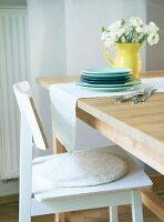 A stack of plates and a bunch of flowers in a yellow jug on a light table runner solid wooden table with a simple wooden chair in the foreground