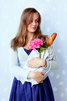A young woman holding a fabric bag filled with a baguette and a hortensia