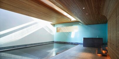 Modern wood panelling in swimming pool room of modern house with dramatic patterns of light and shade on wall