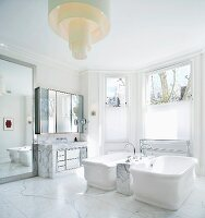 Vintage bathtubs on marble floor with designer ceiling light in spacious, traditional bathroom with bay window