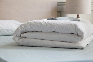 Folded white bedspread on bed