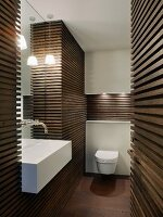 Dark wooden slatted cladding on walls in designer bathroom