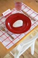 Rustic place setting with red plate, seashell and place name