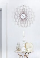 Wall clock with honeycomb frame made from strips of white corrugated cardboard above shabby chic arrangement - candles and sculptural vases on side table