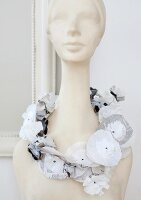 Decorative necklace of flowers made from circles of various papers laid around neck of bust of woman