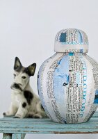 Original vase made from lacquered newspaper and writing paper next to china dog