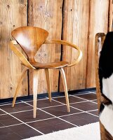 Fifties-style wooden chair in front of wooden wall