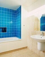 Modern bathroom with blue tiling around bathtub