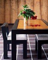 Black-framed table with light wood top, matching chairs and vase of flowers