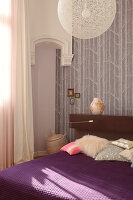 A designer lamp above a double bed in the corner of a bedroom with a traditional atmosphere