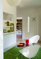 Two white, plastic shell chairs on green, flokati-style rug in open-plan interior with view of dining room