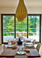Balloon-shaped pendant lamps made from wooden strips above set table in front of terrace door with garden view