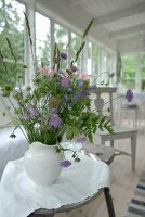 Bouquet of garden flowers in white china jug on side table in loggia